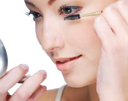 women applying eyelash serum